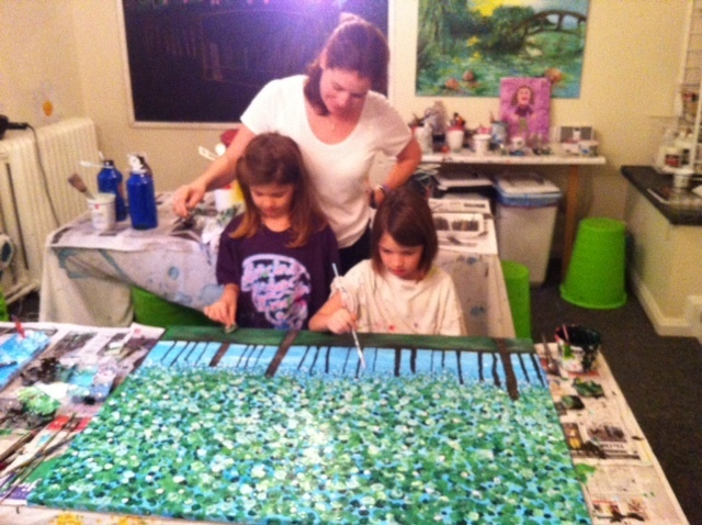 mom and two girls painting trees