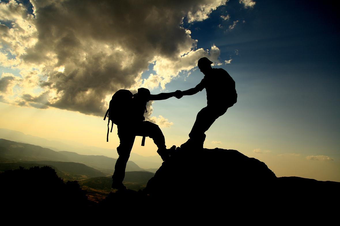Bergsteiger-Zwei-Handreichen-Gemeinsam-Team-Gipfel