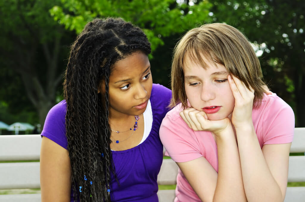 two teen girls helping each other opt