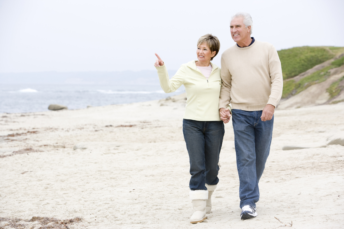 senior-couple-walking-along-beach Htphq0rs
